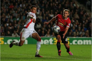 Milton Keynes Dons' Dele Alli clears ball away from Manchester United's James Wilson (right)